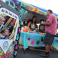 Children pose for a photo at Renasant Bank's hippy-inspired booth at Amory Main Street's ChiliFest.