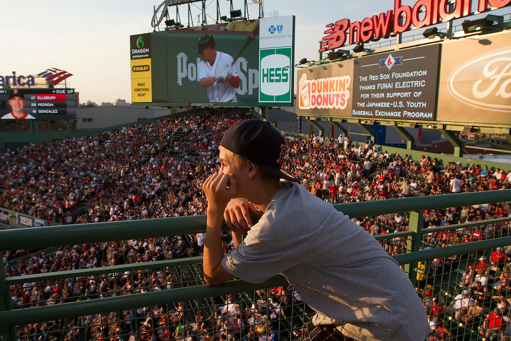 A young man enjoys the view from the standing room section in right field of Fenway Park during summer eveing Red Sox baseball game.