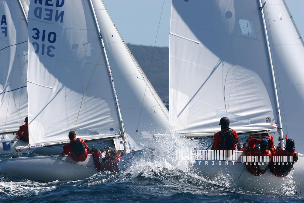 Voile Olympique. Semaine pré-olympique de Hyères. Voile, navigation dans le vent fort, mer agitée. Coup de vent, mer démontée, houle, vague, bateaux à la gîte, écume, vague, embruns, clapot, déferlante, départ au loffe, étrave sous l'écume, équipiers au rappel, grain, orage, coup de mistral, dépression, voile déchirée, compétition, maîtrise, esprit d'équipe, performance, départ au surf, glissade, planning