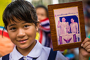 01 AUGUST 2013 - BANGKOK, THAILAND: A Thai school girl holds up a picture of Bhumibol Adulyadej, the King of Thailand, at Siriraj Hospital before the King, 85, was discharged from Bangkok's Siriraj Hospital, Thursday where he has lived since September 2009. He traveled to his residence in the seaside town of Hua Hin, about two hours drive south of Bangkok, with his wife, 80-year-old Queen Sirikit, who has also been treated in the hospital for a year.       PHOTO BY JACK KURTZ