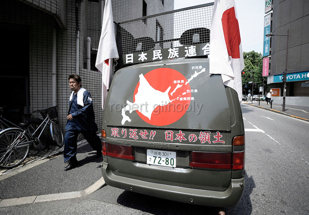 A nationalist man walks past a van decorated with a map showing Japan's disputed islands and a slogan demanding them back from Russia outside Yasukuni Shrine in Tokyo, Japan on 15 Aug. 2008. Wartime prime minister Hideki Tojo - who ordered the attack on Peal Harbor and was charged and hanged as a war criminal after World War II, is enshrined inside the controversial Yasukuni Shrine together with 13 other convicted war criminals, a fact that still angers citizens in China and South Korea, both of which fell vicim to Japan's wartime activities. Aug 15. is the anniversary of Japan's surrender in World War II and 100s of thousands of pilgrims from around the country visit the shrine...Photographer: Robert Gilhooly