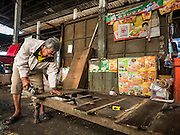 04 JANUARY 2016 - BANGKOK, THAILAND:  A vendor takes apart his daybed in Bang Chak Market after the market closed permanently. The market closed January 4, 2016. The Bang Chak Market serves the community around Sois 91-97 on Sukhumvit Road in the Bangkok suburbs. About half of the market has been torn down. Bangkok city authorities put up notices in late November that the market would be closed by January 1, 2016 and redevelopment would start shortly after that. Market vendors said condominiums are being built on the land.       PHOTO BY JACK KURTZ