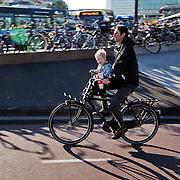 Nederland, Utrecht, 11-04-2011 Fietsen . Een vader met een kind met Nijntje in het voorzitje rijdt op een zogenaamde transportfiets over het fietspad. Foto: Gerard Til/Hollandse Hoogte