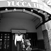 Fearing a storm, Daly takes shelter under the awning of the Yucca Theatre..