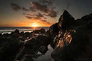 Hand-held grab shot of a wash of golden light over eroded smooth rocks on Anglesey&rsquo;s West coast this evening. <br /> <br /> The skies looked dramatic, numerous clouds being blown rapidly in a strong breeze. The air was cold enough to warrant a winter coat, but anticipating some tidal shots I wore shorts to the beach. As I stood in the sea to make more images I was surprised at how warm the waves were as they wrapped around my legs.