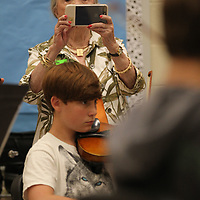 Margaret Anne Murphey makes her way the classroom at Tupelo Middle School and photographs the students during their string class as part of her video segment on the Tupelo Symphony.