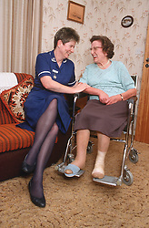 District nurse visiting elderly woman; who is wheelchair user; at home,