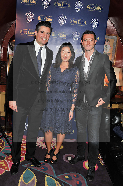 Left to right, EDWARD TAYLOR, BEATRIX ONG and LUKE EVANS at the Johnnie Walker Blue Label and David Gandy partnership launch party held at Annabel's, 44 Berkeley Square, London on 5th February 2013.