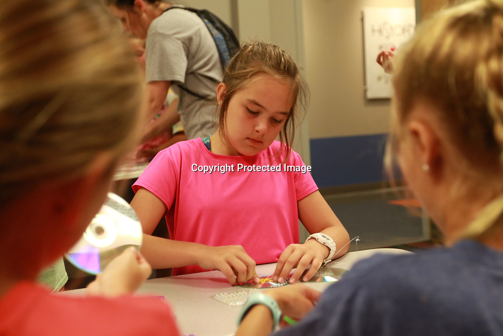 LIBBY EZELL | BUY AT PHOTOS.DJOURNAL.COM<br /> Abby McLarty, 10 decorates her CD with glitter stars during craft time at the Orchard's VBS Wednesday night