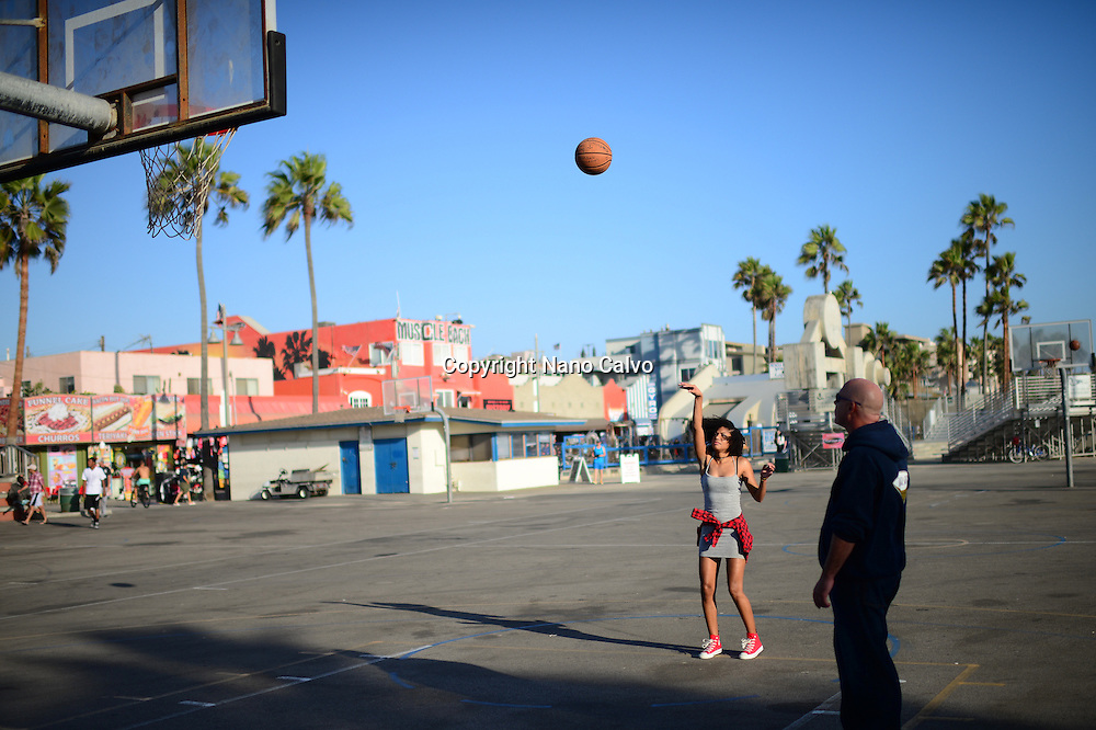 Young couple playing basketball in street court at Venice Beach, California.