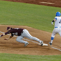 Jun 25, 2013; Omaha, NE, USA; Mississippi State Bulldogs first baseman Wes Rea (35) dives after the ball against UCLA Bruins second baseman Cody Regis (18) during the sixth inning in game 2 of the College World Series finals at TD Ameritrade Park. Regis was safe at first. Mandatory Credit: Derick E. Hingle-USA TODAY Sports