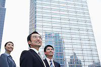 China Hong Kong three business people standing amongst skyscrapers low angle view