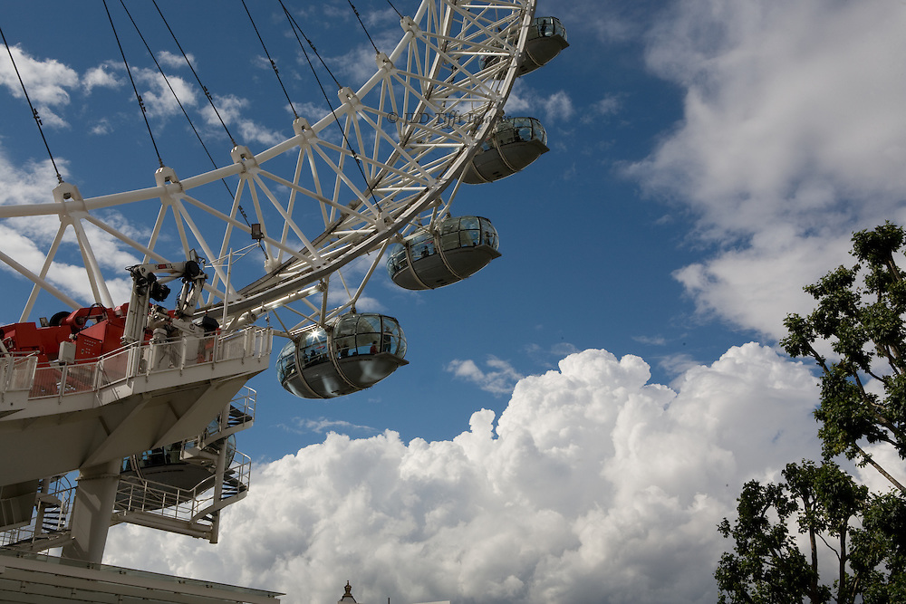 Segment of the circle of the British Airways London Eye, four pods with passengers showing against a bright blue sky with shapely white clouds.