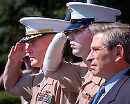 Cpl. James E. Wright, center, along with Deputy Secretary of Defense Paul Wolfowitz, right, and Col. Daniel O'Brien, Commander of Marine Barracks, Washington DC, at left, salute during the presentation of Colors at Award Ceremony in his honor where he was awarded the Bronze Star Medal for heroic achievement in connection with combat operations in Iraq on April 7, 2004 where he and his unit came under heavy attack, he engaged the enemy with his squad automatic weapon continuing to fire until his vehicle was hit with a rocket propelled grenade causing the loss of both hands and injury to his leg. The medal was presented by Deputy Secretary of Defense Paul Wolfowitz. The ceremony was held at the U.S. Marine Corps war Memorial in Arlington, Virginia on June 1, 2004. (Alan Lessig/Times News Service)