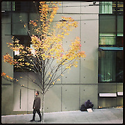 2016 OCTOBER 22 - A man walks past a homeless man down 1st Avenue in downtown Seattle, WA, USA. Taken with Apple iPhone using Instagram App. By Richard Walker