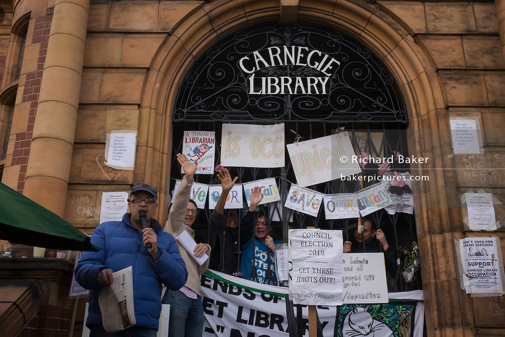 Local campaigners gather outside Carnegie Library in Herne Hill, south London while occupiers remain inside the premises on day 8 of its occupation, 7th April 2016. The angry local community in the south London borough have occupied their important resource for learning and social hub for the weekend. After a long campaign by locals, Lambeth have gone ahead and closed the library's doors for the last time because they say, cuts to their budget mean millions must be saved.