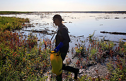 CANADA ALBERTA FORT MCMURRAY 23JUL09 - Greenpeace Canada action coordinator Kenneth Lowyck collects water and soil samples from the tailings pond of the tarsands mining site of CNRL (Canadian Natural Resources Limited) Horizon north of Fort McMurray, northern Alberta, Canada...The tar sand deposits lie under 141,000 square kilometres of sparsely populated boreal forest and muskeg and contain about 1.7 trillion barrels of bitumen in-place, comparable in magnitude to the world's total proven reserves of conventional petroleum. Current projections state that production will  grow from 1.2 million barrels per day (190,000 m³/d) in 2008 to 3.3 million barrels per day (520,000 m³/d) in 2020 which would place Canada among the four or five largest oil-producing countries in the world...The industry has brought wealth and an economic boom to the region but also created an environmental disaster downstream from the Athabasca river, polluting the lakes where water and fish are contaminated. The native Indian tribes of the Mikisew, Cree, Dene and other smaller First Nations are seeing their natural habitat destroyed and are largely powerless to stop or slow down the rapid expansion of the oil sands development, Canada's number one economic driver...jre/Photo by Jiri Rezac / GREENPEACE..© Jiri Rezac 2009
