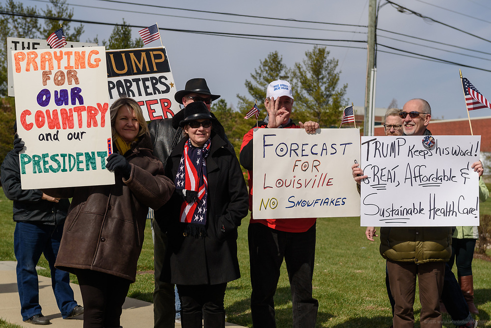 Some of the Trump supporters gather together for a picture, one holding what an opposing protester called a white power symbol. Groups protest The Republican Party's proposed changes to the Affordable Care Act during a visit by Vice President Mike Pence with Kentucky Governor Matt Bevin and business leaders Saturday, March 11, 2017 at Trane Parts and Distribution Center, 12850 Plantside Drive, Louisville, Ky. (Photo by Brian Bohannon)