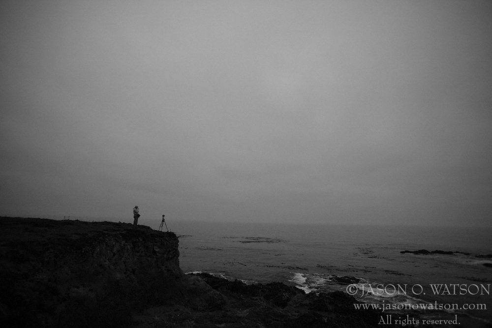 A photographer sets up his tripod at the edge of a cliff near Mendocino, California, USA.