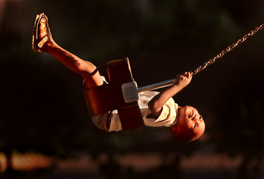 Christopher Braxton age 3, takes a break with a swing at William Land Park as the warm setting sun lights his horizontal body.