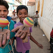 India. Bihar. Bodhgaya, the town where the Buddha sat under a sacred fig tree (bhodi tree) and received enlightenment. Young boys playing with spinning tops.