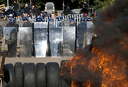 © Licensed to London News Pictures. 19/10/2011. Crays Hill, UK. POlice in riot gear stand in front of burning tyres. Residents at Dale Farm, the UK's largest illegal traveller site being evicted today (19/10/2011) following a long dispute with Basildon Council . Travellers and activist had barricaded themselves in to the site in an attempt to prevent their eviction. Photo credit: Ben Cawthra/LNP