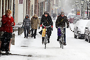 Een vrouw steekt buiten het café op de Oudegracht in Utrecht een sigaret op, terwijl fietsers door de sneeuw proberen te komen met hun inkopen.<br /> <br /> A woman is lighting her cigarette outside a cafe at the Oudegracht Utrecht, while cyclists are trying to get through the snow with their shoppings.