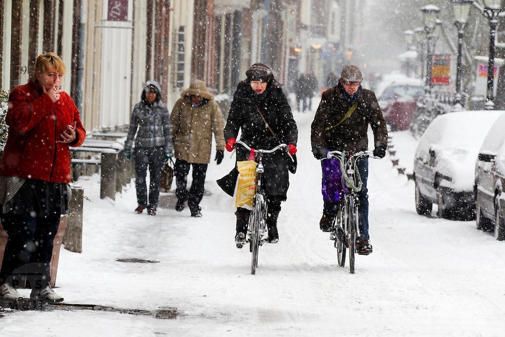 Een vrouw steekt buiten het caf&eacute; op de Oudegracht in Utrecht een sigaret op, terwijl fietsers door de sneeuw proberen te komen met hun inkopen.<br /> <br /> A woman is lighting her cigarette outside a cafe at the Oudegracht Utrecht, while cyclists are trying to get through the snow with their shoppings.