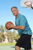 Senior man playing basketball on outdoor court