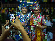 25 SEPTEMBER 2016 - BANGKOK, THAILAND: Residents of the Pom Mahakan community take pictures of Likay performers after a performance in Pom Mahakan Fort. The performance was to support residents of the old fort, who are fighting eviction orders by the city of Bangkok. City officials have made repeated attempts to evict people since Sept 3, 2016, but about 44 families are still living in the community. Likay is a form of popular folk theatre from Thailand. It uses a combination of extravagant costumes, barely equipped stages and vague storylines. The performances depend mainly on the actors' skills of improvisation and the audiences' imagination. There used to be several Likay troupes based in the old fort, but they left the community more than 50 years ago. The troupe that performed Sunday night was an amateur troupe comprised of college students and office workers.      PHOTO BY JACK KURTZ