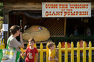 Old Bethpage, New York, USA. September 28, 2014. A mother and two young sons are in front of the 'Guess the Weight of the Giant Pumpkin' booth at the 172nd Long Island Fair, a six-day fall county fair held late September and early October. A yearly event since 1842, the old-time festival is now held at a reconstructed fairground at Old Bethpage Village Restoration. The pumpkin is the First Place winner, and for one dollar, a person gets three guesses of how much the pumpkin weighs, and the winner will win $100.