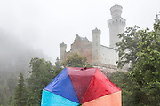 GERMANY, Fussen.  16.08.15 A visitor looks up at the Neuschwanstein Castle as it sits characteristically amongst fairy-tale like mist this afternoon. The miraculous building, built in 1886 for the eccentric Bavarian King Ludwig II, has been the inspiration for countless models, book illustrations and film sets. Rick Findler / Story Picture Agency