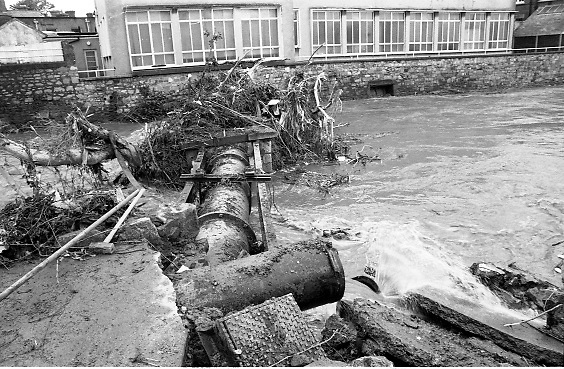 "Flooding at the Dodder..1986..26.08.1986..08.26.1986..28th August 1986..As a result of Hurricane Charly (Charlie) heavy overnight rainfall was the cause of severe flooding in the Donnybrook/Ballsbridge areas of Dublin. In a period of just 12 hours it was stated that 8 inches of rain had fallen. The Dodder,long regarded as a ""Flashy"" river, burst its banks and caused great hardship to families in the 300 or so homes which were flooded. Council workers and the Fire Brigades did their best to try and alleviate some of the problems by removing debris and pumping out some of the homes affected..Note: ""Flashy"" is a term given to a river which is prone to flooding as a result of heavy or sustained rainfall...Image of the watermain crossing the Dodder covered with debris as a result of the deluge."