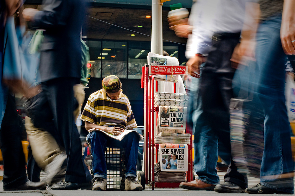 Crisis in the newspaper industry.  New Yorkers and their news reading habits...A newspaper salesman reading the New York Post outside Penn Station, close to the New York Times building on 8th avenue and 41st street...Photographer Chris Maluszynski /MOMENT