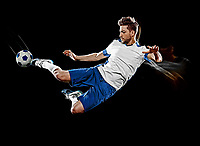 one caucasian soccer player man isolated on black background with light painting speed effect