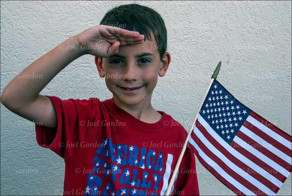 Young boy salutes the flag.<br />