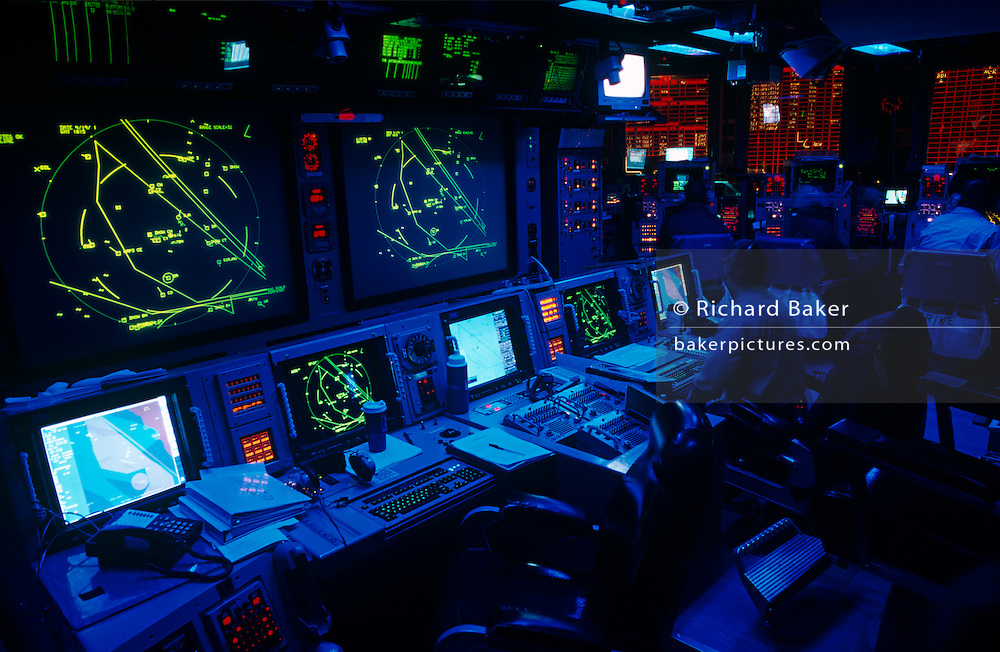 Deep below-decks, we see the highly-classified Conflict Direction Center or War Room on the US Navy aircraft carrier USS Harry S Truman during its deployment patrol of the no-fly zone at an unknown location in the Persian Gulf. This top secret office is used for planning and executing sophisticated tactical electronic warfare that fighter jets and surveillance aircraft engage in from air operations mounted from the carrier. The Truman is the largest and newest of the US Navy's fleet of new generation carriers, a 97,000 ton floating city with a crew of 5,137, 650 are women. The Iraqi no-fly zones (NFZs) were proclaimed by the United States, United Kingdom and France after the Gulf War of 1991 to protect humanitarian operations in northern Iraq and Shiite Muslims in the south.