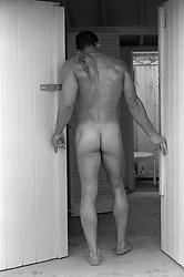 nude man looking into a room