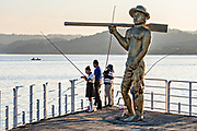 People fish off the town pier next to the Statue of the Fisherman at sunset in Catemaco, Veracruz, Mexico. The town is built along a tropical freshwater lake at the center of the Sierra de Los Tuxtlas mountains, is a popular tourist destination and known for free ranging monkeys, the rainforest backdrop and Mexican witches known as Brujos.