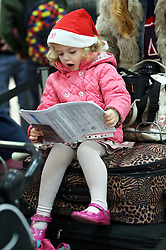 A young girl with her passport and itinerary  at the ready as she waits at check in with her family at London Gatwick airport with her family as the Christmas getaway starts Friday, 20th December 2013. Picture by Stephen Lock / i-Images