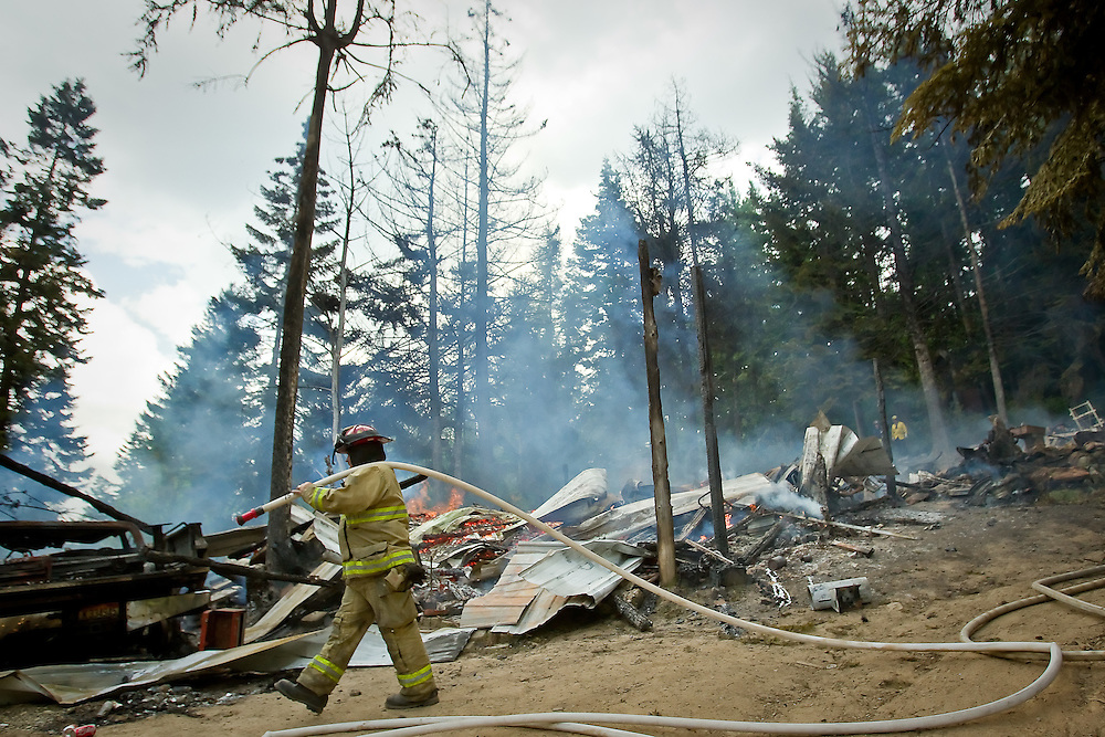 Kootenai County firefighter Jeryl Archer drags a fire hose to a hot spot near the top of Blossom Mountain, south of Post Falls, where a home was destroyed Thursday.