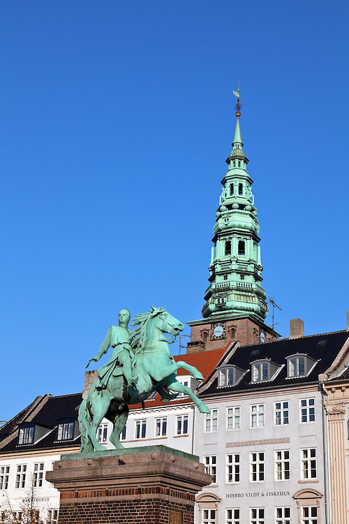 The equestrian statue of Bishop Absalon, the founder of Copenhagen in 1167, dominates the Hojbro Plads (Hojbro Square) in the heart of that city's downtown. The ornate tower of Nikolaj Church (no longer active) fills the background.