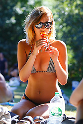 © Licensed to London News Pictures. 23/08/2016. London, UK. A women eats ice-cream whilst sunbathing in Hampstead Heath Park in north London as they enjoy August's last heatwave on Tuesday, 23 August 2016. Photo credit: Tolga Akmen/LNP
