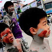 A family waits in line for a mud slide at the 11th Annual Mud Festival in Boryeong, South Korea, 2008.