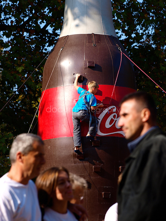A child practices wall climbing on inflatable Coca Cola structure in Margaret Island park, Budapest, Hungary.