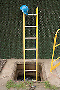manhole with ladder and a Con Edison hardhat
