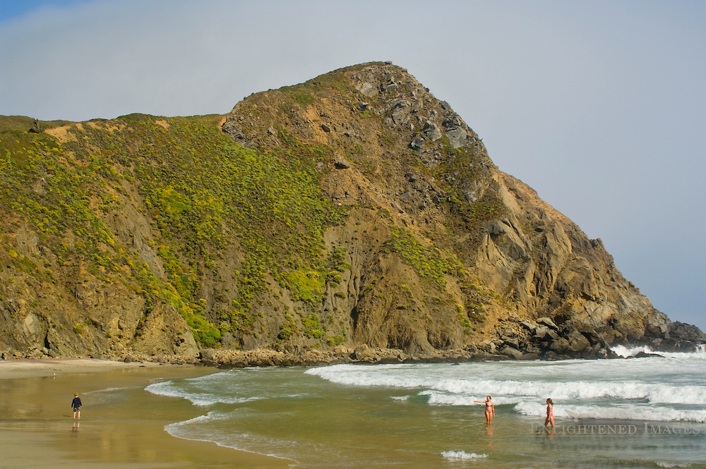 Young boy and girls playing on sand and in waves below coastal cliff at Pfeiffer Beach, Big Sur Coast, Monterey County, California