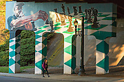 A woman walks past the Asheville Mural Project painted on the overpass under Highway 240 Bridge connecting Lexington and Broadway in Asheville, North Carolina.