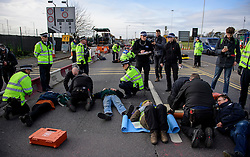 "© Licensed to London News Pictures. 19/11/2016. Heathrow, UK. Police use cutting equipment to detach activists form a road surface. A group of activists stage attach themselves to a road surrounding  Heathrow Airport, during a demonstration against the expansion of Heathrow Airport and the building of a third runway. Some activists  threatened ""direct action"". Photo credit: Ben Cawthra/LNP"