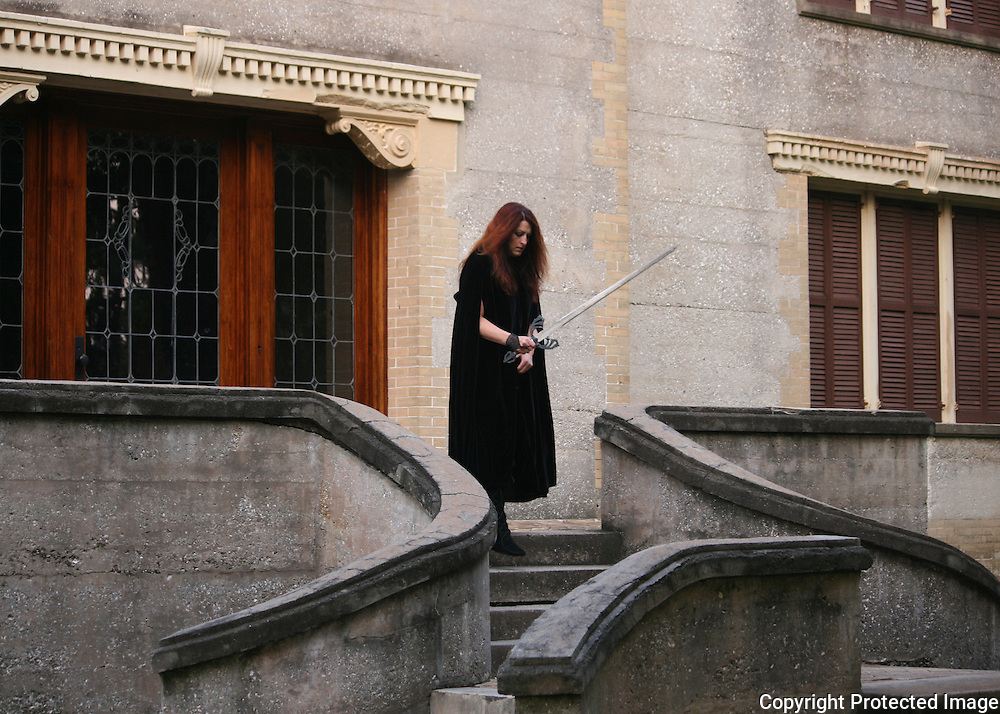 Armed red head woman descending steps of haunted house Jekyll Island
